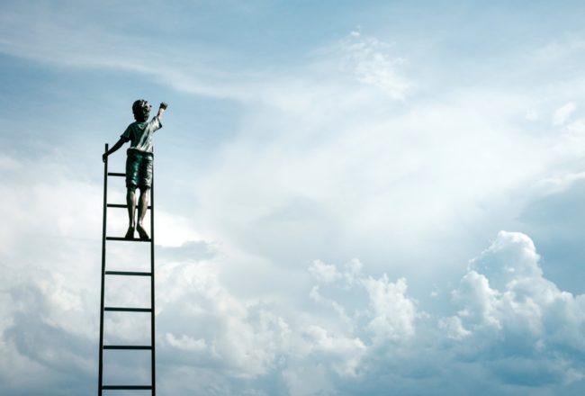 Pojke som står på en stega och tittar mot molnen